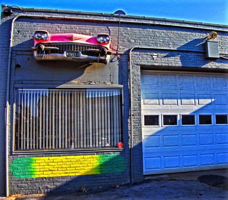 オハイオ州アクロンで自動車修理店の HDD イメージ。建物は建物に埋め込まれたキャデラック フロント エンド 1950 年代ピンク 報道画像