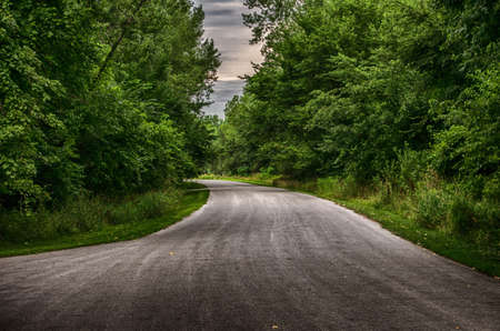 winding road through a forested park Stock Photo