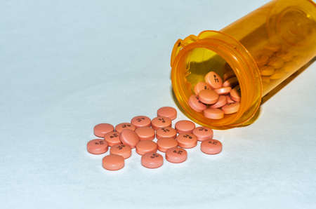 Orange pills spilled from a prescription bottle