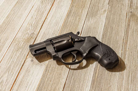 Black .38 special revolver on a wood table