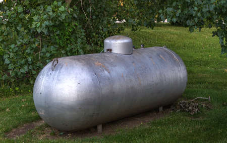 contain: Propane gas container in rural area Stock Photo