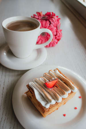 Millefeuille Napoleon with coffee in cafe. Exquisite dessert with fresh berries on white background. French Vanilla Raspberry Mille-feuille on the dish