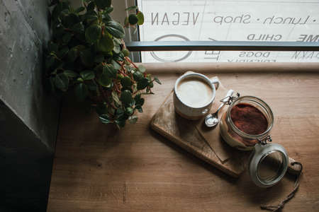 High angle view of tiramisu in glass cup with coffee cappuccino. In vegan shop, local cozy cafe. Wooden background, candid style. Copy space