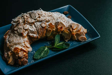 Tasty croissant with powdered sugar and mint on the plate on a dark background