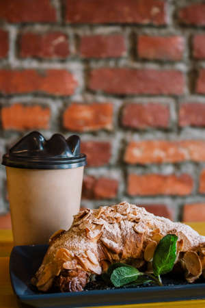 Take away coffee and fresh croissant with mint on wooden background. Cardboard cup with face cap concept. Stock fotó