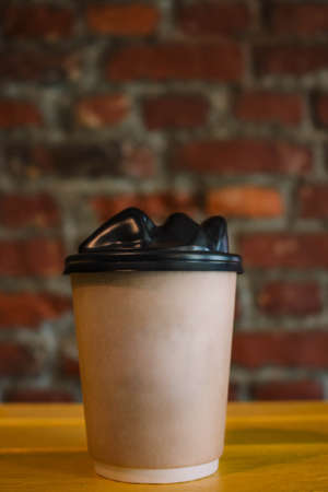 One focused take away brown paper cup with black cap with the face presented in front, on a simple gray background