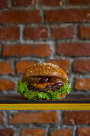 Craft beef burger with pear and cherry on wooden table isolated on brick wall background. Stock Photo