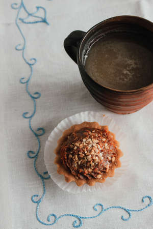Shortcake baskets with walnuts and condensed milk. Russian style. Homemade baking on a white napkin. Dessert - biscuits with coffee cappuccino Stock fotó