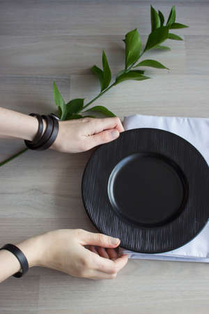 Black plate on white wooden background. With plant and napkin,top view. Empty plate for serving