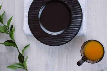 Black plate on white wooden background. With plant and napkin,top view. Empty plate for serving with orange juice