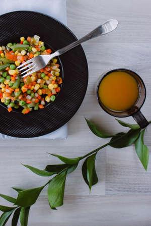 Frozen fried vegetables on black plate. Vegan breakfast with juice. Vegetables food mix on white wooden background