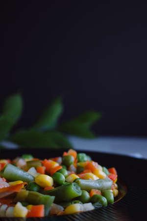 Frozen fried vegetables on black plate. Vegan breakfast. Vegetables food mix on white wooden background.