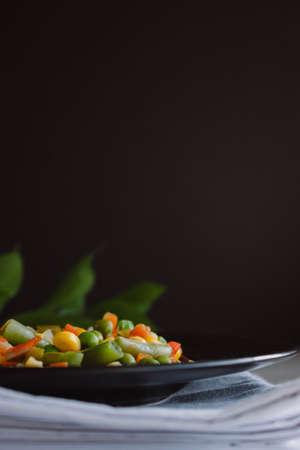 Frozen fried vegetables on black plate