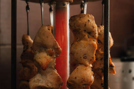 Grilled meat on the electric grill. Vertical BBQ for cooking. Barbecue set with chicken shashlik