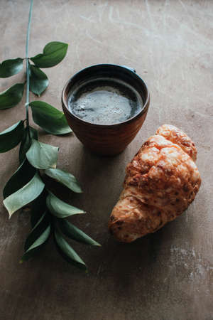 Cappuccino coffee and croissant on wooden background on the table. Perfect breakfast in the morning. Rustic candid style.