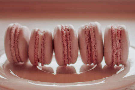 Strawberry macarons closeup. Fresh and colourful on pink background