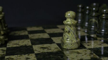 Chess game. White pawn defeats black pawn. Selective focus. Chess pawn defeated pawn. Details of chess piece on black background. Stock Photo