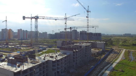 Construction site workers, overhead view of construction site with large crane.