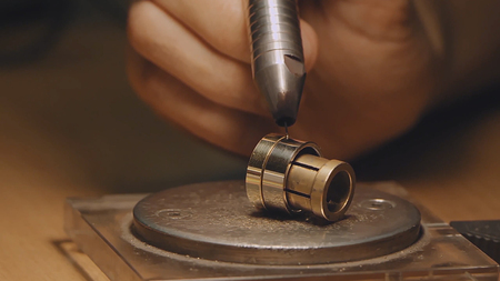 Jeweler working with wax model ring in his workshop. Detail shot with low depth of field. Jeweler making handmade jewelry on vintage workbench. Stock Photo