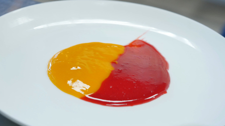 Smearing jam on a plate. Two kinds of jam smeared on the plate with a spatula Stock Photo