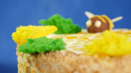 Beautiful honey cake decorated with bees of cream. Beautiful honey cake, closeup. Stock Photo