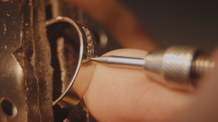 The jeweller is setting a precious stone. Craft jewelery making. Ring repairing. Putting the diamond on the ring. Macro video. Craft jewelery making with professional tools. Putting the diamond on the ring. Macro photo.