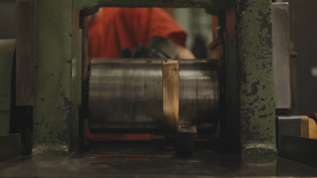 heavy industry: Hand-rolled gold bars. Factory worker processing roll of steel sheet. METAL INDUSTRY. Rolling mill machine for rolling steel sheet. Tilt shift effect 4K