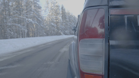 Headlight closeup on snowy roads. The car rides on a snow-covered road
