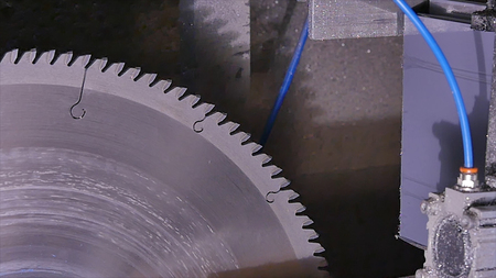 Circular saw for cutting aluminum. Sawing metal. Pendular electric saw for metal cutting, Metal sawing close up. Angel grinder make a flash sparks. Industry