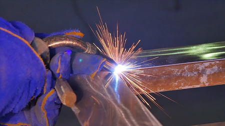 Metal Welding with sparks and smoke. Worker with protective mask welding metal. Welder joins metal parts. A process using a semi-automatic welding. Welding steel. Industrial Worker at the factory welding closeup. Industrial welding automotive. Industy in
