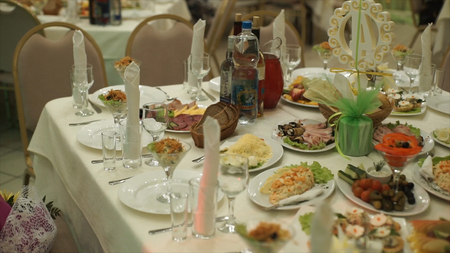 Table with food and drink. Catering table set service with silverware and glass stemware at restaurant before party. Table with the spread-out devices and food. Christmas tree