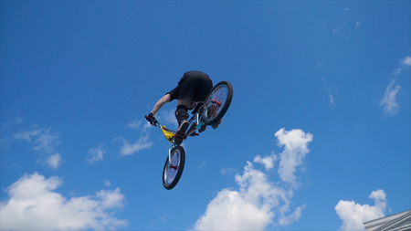 Young man on BMX bike jumps. Man doing twists and tricks on bmx in slow motion blue sky background.
