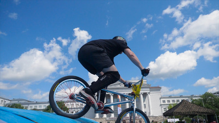 Young man on BMX bike jumps. Man doing twists and tricks on bmx in slow motion blue sky background