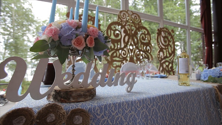 wedding feast: Wedding table at a wedding feast decorated with bridal bouquet. Banquet hall. festive table for the bride and groom decorated with cloth and flowers. Table set for bride and groom. Wedding