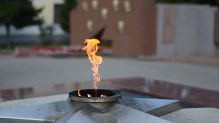 Eternal Flame - symbol of victory in World War II. Burning eternal flame and star at mass tomb of soldiers. Eternal Flame at the memorial to fallen defenders the motherland. Eternal fire burns against a granite roadway. Fire