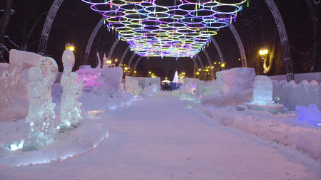 Winter night in the ice park. snow village. People and baby Walk In Ice Town During Snowfall. Stock Photo