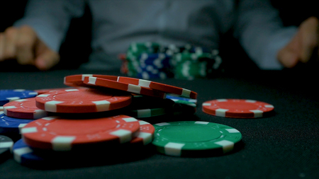 stakes: Close-Up of Man Throwing a Poker Chips in slow motion. Close-up of hand with throwing gambling chips on black background. Poker player increasing his stakes throwing tokens onto the gaming table. Stock Photo