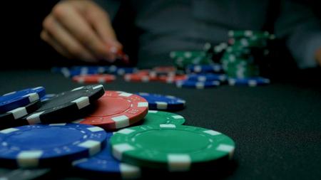 Werfen Sie die blauen Chips in Poker. Blaue und rote spielende Schürhaken-Chips im reflektierenden schwarzen Hintergrund. Nahaufnahme von Poker-Chips in Stapeln auf grünem Filz Karte Tischoberfläche in Zeitlupe