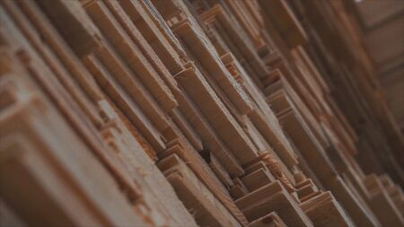 Background of the square ends of the wooden bars. Wood timber construction material for background and texture. close up. Stack of wooden bars. small depth of field. plywood boards on the furniture industry.