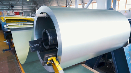 Rolled steel. Stack of rolls, Cold rolled steel coils in action. Galvanized Steel Sheet and rusty rim. Cold rolled steel coils. he drum turns the metal sheets in the production. Industrial Stock Photo