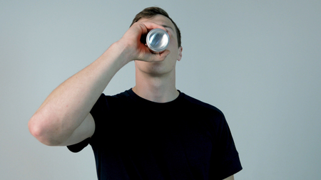 Young man drinking soda. Young man in black shirt drinking soda, on a white background