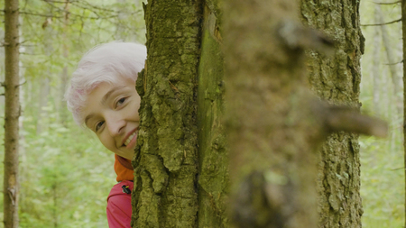 Young attractive smiling woman looking behind the tree. Blonde girl check and looks from behind a tree In the autumn forest