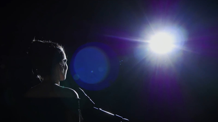 Girl in long gown performing on stage. the girl singing on the stage in front of the spotlight. Silhouette of singer standing on stage at microphone in night club