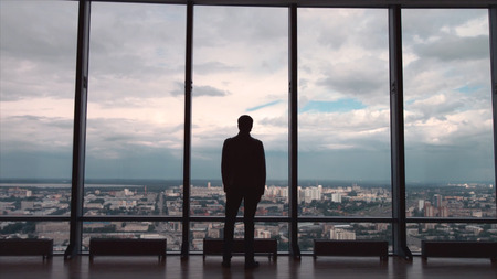 Rear view of businessman in an office with panoramic city view. Businessman admires the city from the panoramic Windows in the city centre 版權商用圖片