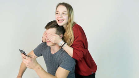 cute guy: beautiful happy smiling woman covering eyes with her hands of handsome young man in fun mood
