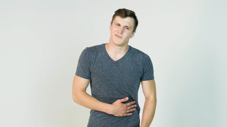 Young man having a stomachache on white background. Young man holds the stomach, it hurts