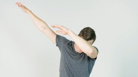 Young man makes a dab or flex its dance move on white background