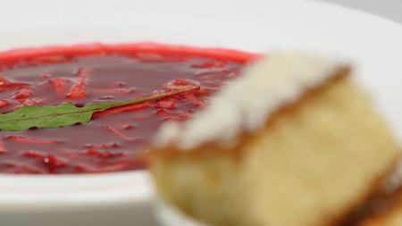 Red Borsch with meat in plate. A delicious red borscht with sour cream and herbs on a white plate. Traditional Ukrainian beetroot soup - red borsch and dumplings with garlic