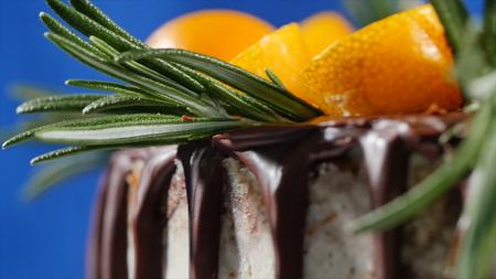 Cake decorated with rosemary, kumquat and gingerbread cookies. Cake decorated kumquat and cinnamon