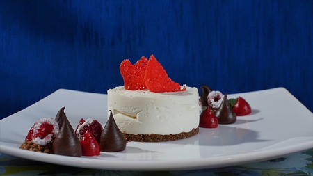 Cake with meringue frosting and raspberries. Meringues Pavlova cakes with fresh raspberry and blueberry on a dark blue background. Big meringue zephyr on plate